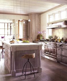 Tone–on-Tone Kitchen by John Saladino. Muted stainless cabinets flank the range. Washed rift oak wood. Ruby brown French range.