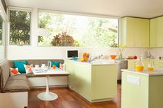 Bright kitchen.  Built in seating.  Corner bench.  Pale yellow.