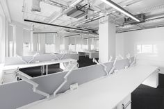 See the exposed lighting and ductwork which is offset nicely by the white desks, fixtures, fittings and walls