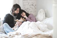 Foto com clima aconchegante de outono/inverno. Casal (Melina Souza e Beni) sentados na cama cheia de cobertas e travesseiro fazendo carinho no cachorrinho (yorkshire Spock). Post inspirador compartilhando pequenas felicidades do dia-a-dia.