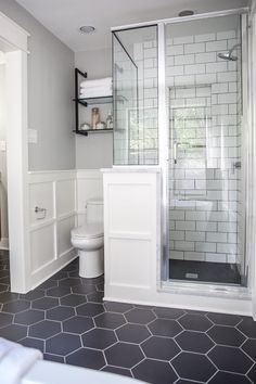 We used large, hexagonal flooring throughout the whole bathroom. I love the way it paired with the classic white subway tile we used in the shower. remodel A Master Bathroom Renovation Bathroom Grey, Bathroom Renos, Bathroom Flooring, Bathroom Vanities, Bathroom Cabinets, Bathroom Interior, Dark Floor Bathroom, White Subway Tile Bathroom, Design Bathroom