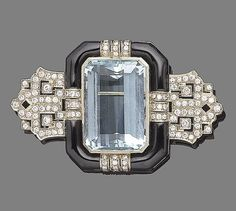 An aquamarine, enamel and diamond brooch.  The large step-cut aquamarine within a black enamel surround, highlighted with rows of brilliant-cut diamonds, to pierced geometric similarly-cut diamond terminals, diamonds approx. 1.20cts total, length 5.7cm. Art Deco or Art Deco style.