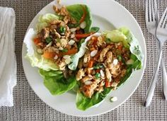 Spicy Chicken Lettuce Wraps  2T olive oil  1teaspoon sesame oil  1lb ground chicken  1cup chopped shiitake mushrooms  1 shallot, chopped  1cup matchstick-sliced carrots  1teaspoon minced garlic  1/4cup sliced almonds, plus more for garnish  3T soy sauce  2T brown sugar  1to 2 T sriracha  1T rice vinegar  1 tsp ginger  1 head bibb or butter lettuce