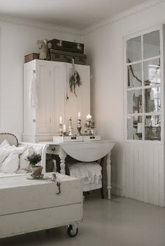 An all white room with white vintage furniture but natural old suitcases.