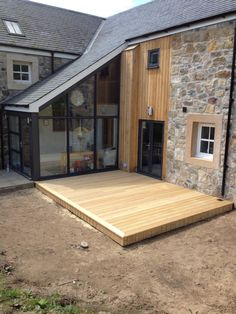 Larch cladding against old stone house