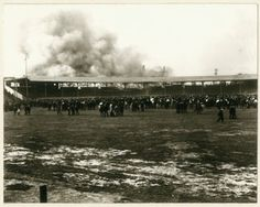 Fire in the grandstand at League Park (Robison Field), Vandeventer Avenue and Natural Bridge Road, 4 May 1901. Horizontal photograph showing billowing smoke and fire near the rear of the grandstand of a baseball stadium. A crowd of spectators watches from the playing field.