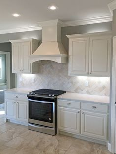 Off White Kitchen Backsplash kitchen with off white cabinets, stone backsplash and bronze