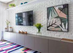 Sala de TV | Tijolinho branco da sala da Arte em Ladrilhos. Móvel executado pela Solução Marcenaria. Adornos da Rosa Kochen (Foto: Lília Mendel/Divulgação)