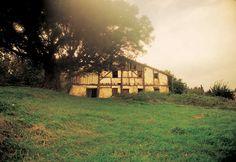Basque. The Balanzategi Haundi farmhouse (Zarautz) is protected by the shade of a stout evergreen oak. © Xabi Otero