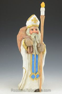 """""""Saint Nicholas holding candle staff measuring 10.6 inches tall. A hand crafted Santa Claus figure, carved from solid wood. Designed, carved by hand, painted, finished and signed by Russell Scott."""""""