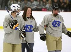 """Rachael Cronk, mother of 5-year-old cancer patient Caroline """"Calle"""" Cronk, is escorted onto the ice by Norwell's Kassidy Nadeau, left, and Tori Dinger during a high school hockey game and fundraiser for Calle, Wednesday at The Bog in Kingston. Rachael Cronk dropped the ceremonial first puck in both the Norwell girls and boys hockey games."""