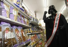 """The force is strong with these snacks - what a savings! (A person dressed as Darth Vader stands in a convenience store during a promotional event for """"Star Wars Celebration Japan"""" in Tokyo on July 1, 2008.)"""