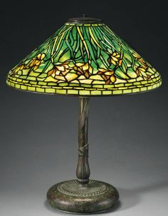 TIFFANY STUDIOS A 'Daffodil' Leaded Glass and Bronze Table Lamp, circa 1910 24¾ in. (62.8 cm.) high, 20¼ in. (51.4 cm.) diameter of shade shade stamped TIFFANY STUDIOS NEW YORK, base stamped TIFFANY STUIODS NEW YORK 6004