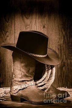 Picture of American West rodeo cowboy black felt hat atop worn western boots and spurs with old ranching rope in an antique wood barn in nostalgic vintage sepia stock photo, images and stock photography. Cowboy Up, Cowboy And Cowgirl, Cowgirl Boots, Western Boots, Cowboy Theme, Rodeo Cowboys, Real Cowboys, Cowboys And Indians, Danse Country