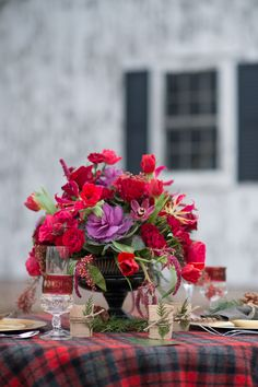 jewel toned centerpiece, arranged in a footed compote urn vase. Perfect for a winter wedding. Plaid linen. Red and purple palette. Kale, garden roses, tulips, anemones, spray roses, amaranthus, etc. Red, purple, green, burgundy, eggplant flowers. Rustic wedding.