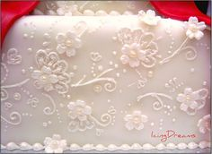 Red Filigree Close up This is a close up shot of the wedding cake just to show the piping detail. the flowers were embossed just slightly. The piping was fairly simple swirls and some brush embroidery which im trying to work on. Alot like henna design =) Painted over with luster dust