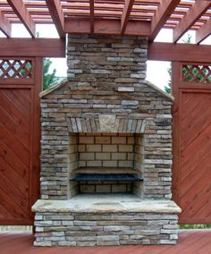 Outdoor custom stone fireplace with pergola and privacy fence