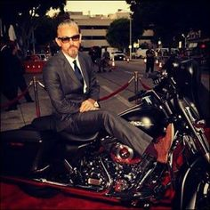 Man in a suit on a motorcycle. Mm.