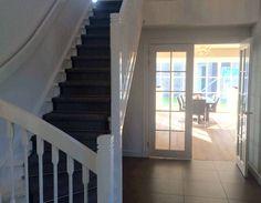 Openslaande deuren vanuit hal en trapdetail met daarachter  deuren naar tuin