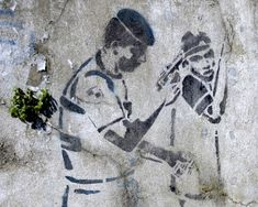 Graffiti of a police officer holding a gun to a man's head