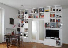 Per dividere cucina e soggiorno sfruttando al massimo lo spazio per contenere, viene prevista una porta scorrevole inglobata in una libreria a ponte. Con il preventivo.