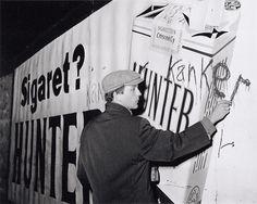 """Robert Jasper Grootveld bekladt tabaksreclame met tekst: """"Kanker"""", Amsterdam, 12 december 1961 Foto Ben van Meerendonk / AHF, collectie IISG, Amsterdam"""