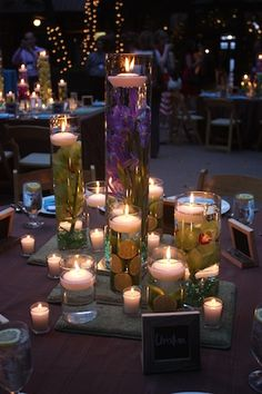Great idea to use tall vases filled w/ flowers/water - floating candle on top and surrounded by votives (I dont love the styling here, but the concept is affordable and sparkly!)#Repin By:Pinterest++ for iPad#