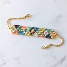 Bracelet en perles tissées à la main, au motif géométrique composé de triangles multicolores et doré. Une fine chaîne boule en plaqué or termine le bracelet, joli petit détail : le rappel des perles au niveau du fermoir.