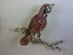 """The Queen`s Ruby bird brooch as pictured in Angela Kelly`s book. I have never seen a picture of the Queen wearing this brooch. The Queen Mother did receive a wedding gift in 1923 from Mr & Mrs Olaf of Hambro """"a jewelled singing bird"""". Maybe this is it but quite likely not??"""