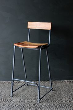 The Soho bar stool is a solid graphite grey metal and wood stool The Soho bar stool is a robust stylish chair with a Shisha wood base and back plate