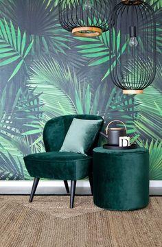 Ran an die Wand! Das saftige Grün erinnert uns an Avocados, Macarons und Tropen-Prints und kommt jetzt auch im Interior ganz groß raus. Eine Tapete mit Palmen-Print versprüht echte Tropen-Eleganz in Deinem Zuhause. Kombiniert mit modernen Interior-Pieces ist der Tropen Look für Dein Wohnzimmer perfekt. // Tapete Kissen Teppich Grün Green Wanddeko Ideen Wohnzimmer Sessel Samtsessel Pouf Leuchte Wandfarbe Trend #Tapete #Wandfarbe #Ideen #Wohnzimmer #Samtsessel #Sessel #Samt #Trend