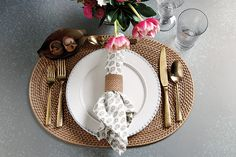 Rattan placemat, white dinnerware, and pink flowers