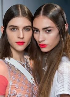 I think their lips are all wrong...both girls have muted cool looks..hair and eyes...and then this crazy bright orange red lip...if they wanted dramatic lips...I would have chosen a rich berry or cool plum with lip liner to define the shape of their mouths.