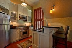 A small kitchen with a two-tier island and bead board accents on the cabinet. A door on the right wall leads out to the backyard. The walls and ceiling are covered in a subtle print. Foliage on yellow for the walls, dots on white on the ceiling.