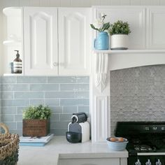 Kitchen with pressed metal and subway tile splashback and Smeg cooker. Vintage and new accessories including pretty blue mason jar.