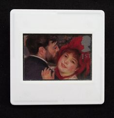 This Renoir postage stamp was issued in 1995 as part of a set of ten Royal Mail stamps called 'Greetings Clown'. The unused stamp shows a close up of Renoir's, 'Danse a la Campagne,' painted in 1883. This delightful image of a couple dancing is encased in a vintage slide mount, with glass, making this a unique piece of jewellery.