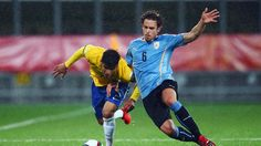 Danilo of Brazil is challenged by Diego Poyet of Uruguay