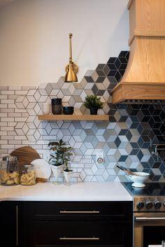 Kitchen remodel, light oak range hood with oak floating shelves, gold lighting, black cabinetry
