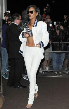 The singer wore a men's Roberto Cavalli white bomber jacket, coordinating pants, and a black-and-white bra top from her Rihanna for River Island collection while out at Cirque Du Soir in London earlier this year. Rihanna Street Style, Street Chic, Rihanna Riri, Rihanna Outfits, Edgy Outfits, Beyonce, London Outfit, India Fashion, Mens Fashion