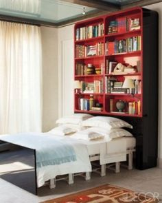 Unique Bedrooms - Crazy Bedroom Design - ELLE DECORA REMOTE CONTROL PULL-OUT BED In this library/guest room, the remote control–operated bed slides out from the bookcase; the linens and cashmere throw are by Schweitzer Linen. Murphy-bett Ikea, Beds For Small Spaces, Shelves In Bedroom, Bookshelf Headboard, Bookshelves, Bookshelf Design, Bookcase Decorating, Red Bookcase, Bookshelf Ideas