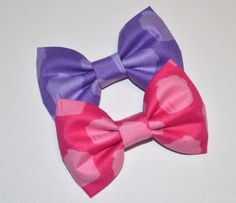"""Set of two bows measuring approx. 2""""x3"""" attached to a single prong alligator clip."""