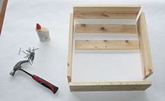 Step 4:  Using the cut boards from step 3, assemble the bottom of the step stool using the image as a guide. Place the cross supports in the middle to act as an anchor, about 10 inches from the back edge. Attach the pieces together with glue and finishing nails.