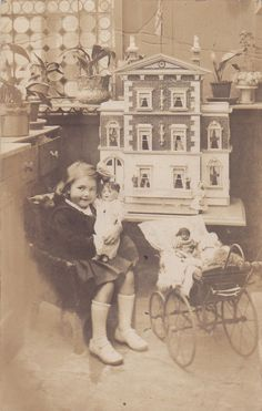 Original Vintage Real Photo Postcard... Girl with her doll, dollhouse and toys.