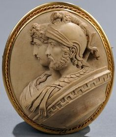 Carved Double-Portrait Lava Cameo Brooch Of Mars And Venus, The Subjects Bust-Length In High Relief And Wearing Classical Roman Dress, Set Within A Gold-Tone Metal Mounting, Figures Identified On The Reverse - Italy   c.1851-1900