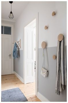 Beautiful modern and Scandinavian inspired entryway with a half-painted wall and some wooden coat hooks. Flur ♡ Wohnklamotte Beautiful modern and Scandinavian inspired entryway with a half-painted wall and some wooden coat hooks.