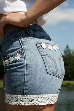 DIY upcycle worn out jeans into cutoffs with a girly flare by adding lace over bottom stitch and some cute flowers around pockets TOO cute!