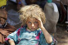 A Yazidi girl rests at the Iraqi-Syrian border.