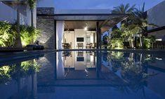 Vue sur cette jolie maison de ville éclairée dans la nuit à partir de la piscine