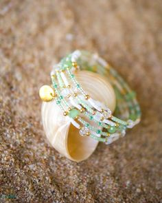 Inspired by the enchanting green and white hues formed by the ebb and flow of seawater, Sea Foam is a handmade spiral bangle made with radiant 22K Gold Plated beads, beautiful glass crystal beads and fine glass seed beads in shades of pastel green and white.