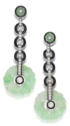 A pair of Art Deco onyx, jadeite jade and diamond pendant earrings, circa 1925. Each designed as a carved jadeite jade bi suspended from a line of old European-cut diamonds and circular onyx links and completed by a jadeite jade and diamond surmount of floral motif; mounted in platinum; length: 2 7/8in. #ArtDeco #earrings